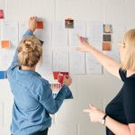Female Business Owner With Intern Looking At Designs On Wall In Start Up Fashion Business
